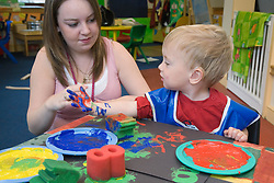 Nursery teacher and boy playing with paints at an early start unit ran by the Nottingham Royal Society for the Blind (NRSB),