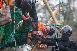 Bailiffs suspended from a large cherry picker work to remove Dan Hooper, widely known as Swampy during the 1990s, who is sitting on a bamboo tripod positioned in the river Colne on 8th December 2020 in Denham, United Kingdom. The climate and roads activist had occupied the tripod the previous day in order to delay the building of a bridge as part of works for the controversial HS2 high-speed rail link and a large security operation involving officers from at least three police forces, National Eviction Team enforcement agents and HS2 security guards was put in place to facilitate his removal.