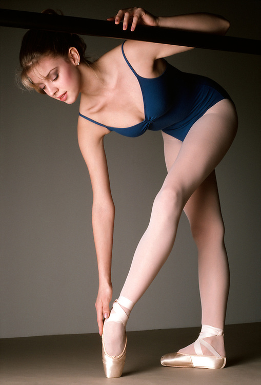 Ballerina bent over and touching her foot and holding onto the exercise bar
