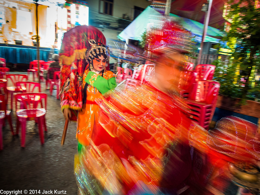 "18 AUGUST 2014 - BANGKOK, THAILAND:   Members of the Lehigh Leng Kaitoung Opera troupe walk through the crowd to the shrine at the beginning of a performance at Chaomae Thapthim Shrine, a small Chinese shrine in a working class neighborhood of Bangkok. The performance was for Ghost Month. Chinese opera was once very popular in Thailand, where it is called ""Ngiew."" It is usually performed in the Teochew language. Millions of Chinese emigrated to Thailand (then Siam) in the 18th and 19th centuries and brought their culture with them. Recently the popularity of ngiew has faded as people turn to performances of opera on DVD or movies. There are still as many 30 Chinese opera troupes left in Bangkok and its environs. They are especially busy during Chinese New Year and Chinese holiday when they travel from Chinese temple to Chinese temple performing on stages they put up in streets near the temple, sometimes sleeping on hammocks they sling under their stage. Most of the Chinese operas from Bangkok travel to Malaysia for Ghost Month, leaving just a few to perform in Bangkok.      PHOTO BY JACK KURTZ"