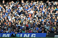 Chelsea fans attempt to block the sun from their eyes. Barclays Premier league match, Chelsea v Manchester Utd at Stamford Bridge Stadium in London on Saturday 18th April 2015.<br /> pic by John Patrick Fletcher, Andrew Orchard sports photography.