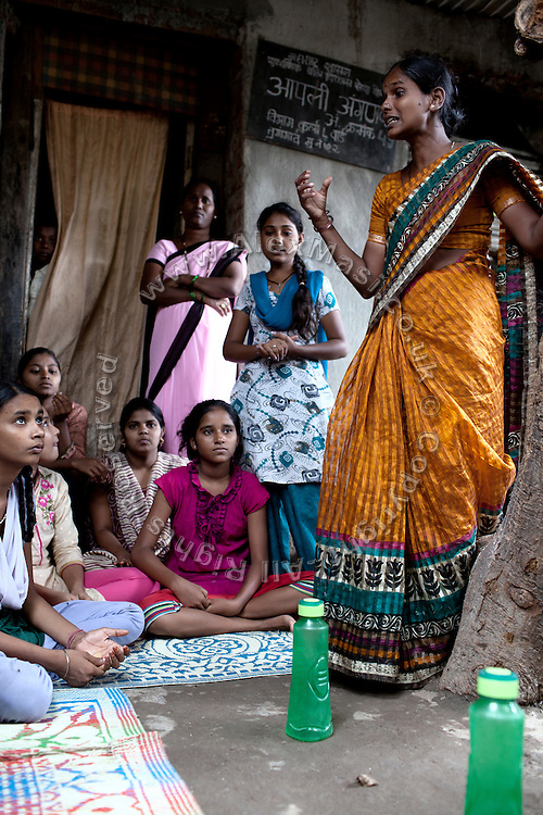 Anita Suresh Kasbe, 41, the Unicef community facilitator is teaching the girls attending the Unicef-run 'Deepshikha Prerika' project inside the Milind Nagar Pipeline Area, an urban slum on the outskirts of Mumbai, Maharashtra, India.