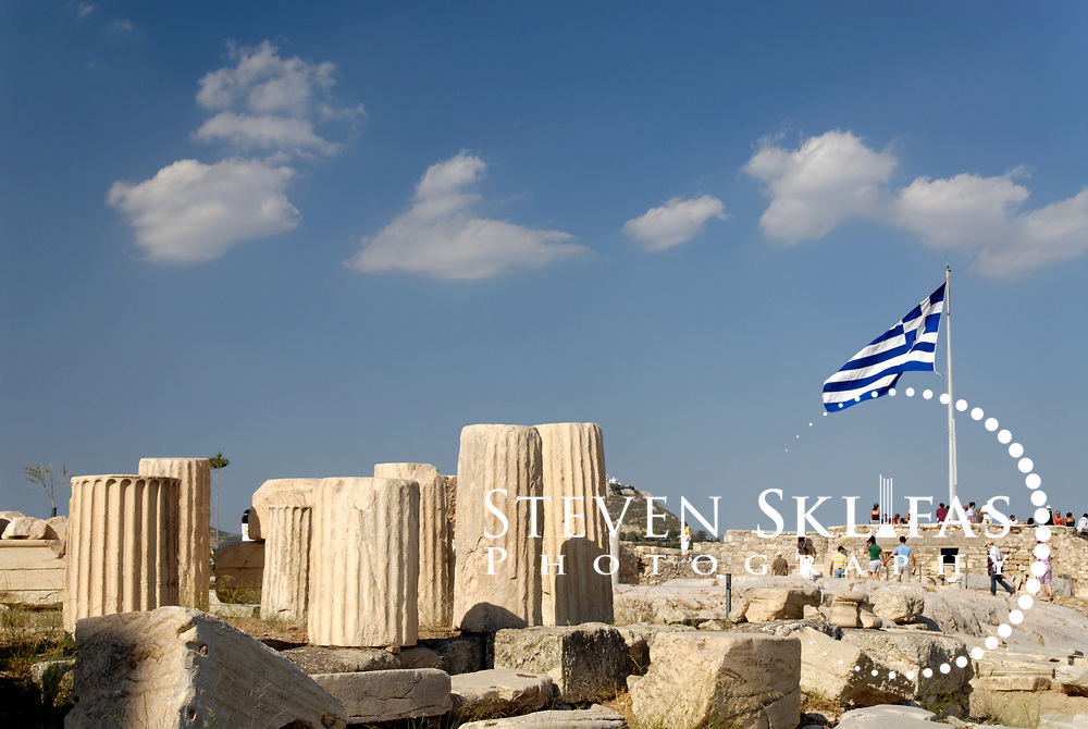 Acropolis. Athens. Greece. View of the Greek flag and various sized fluted column pieces or drums on the Acropolis. The Acropolis of Athens and its monuments are a UNESCO World Heritage Site.