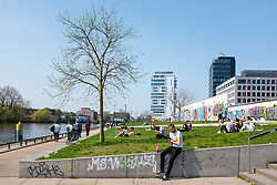 View of people in riverside park beside original section of Berlin Wall at East Side Gallery in Friedrichshain, Berlin, Germany