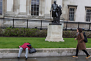 A tourist rushes to help an elderly lady who lies unwell at the foot of the statue of George Washington in Trafalgar Square, Westminster, on 9th April 2019, in London, England.