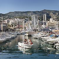 Monaco, 6 augustus 2009. .De haven van Monaco, gelegen in het stadsdeel Condamine, is gekend door de vele superjachten en cruiseschepen die er aangemeerd liggen, het een al luxueuzer dan het andere. De Grand Prix van Monaco begint en eindigt hier ieder jaar..Het staatje Monaco grenst aan Frankrijk en de Middellandse Zee. Monaco heeft een oppervlakte van nog geen 2 km en heeft ongeveer 32. 000 inwoners. Daarmee is Monaco het dichtstbevolkte land ter wereld. Monaco telt twee steden: Monte-Carlo en Monaco-ville, de oude stad..Foto:Jean-Pierre Jans..Monaco, 6th august 2009. The Port of Monaco in the Condamine District, with many very luxurious super yachts  and cars. A small yacht is leaving the harbour.