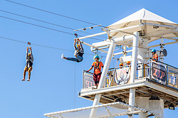 © Licensed to London News Pictures. 15/09/2019. Brighton, UK. Members of the public take advantage of one of the last days of sunshine to take a ride of the Zoo Wire attraction on the beach in Brighton and Hove. Photo credit: Hugo Michiels/LNP