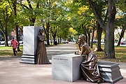 Jogger by statues of Phillis Wheatley and Abigail Adamis at Boston Women's Memorial in Commonwealth Avenue Mall, Boston, USA