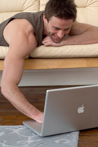 man on sofa working on a laptop computer, home office, working from home<br />