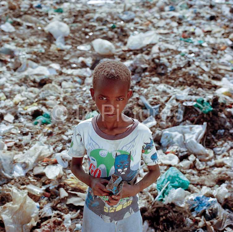 A shoeless child wanders on to Eldoret's main dump undeterred or unaware of  the constant  risk of cuts from broken glass and infection from needles dumped here by the hospital . ( model release unavailable) <br /> <br /> The Dump nick named by the locals, ironically, as 'California' is home to a community of Kenyans who make their living here recycling plastic, metal charcoal and even scavenging for food either for themselves or for their pigs. The average adult here earns about 150 -200 Kenyan shillings (£1-1.30) The consequences for those who work here on a regular basis including woman and children as young as 7 is  tough; with disease, injury, substance abuse and even the threat of violence an everyday reality.