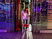 """22 MAY 2014 - BANGKOK, THAILAND:  A waitress in a bar on Soi Cowboy, one of Bangkok's """"adult entertainment"""" districts, closes her bar after the army announced an overnight curfew. The Thai army suspended civilian rule, suspended the constitution and declared the """"military takeover of the nation."""" The announcement came just before evening as a meeting between civilian politicians and the army was breaking up with no progress towards resolving the country's political impasse. Civilian politicians were arrested when the meeting ended. The army also declared a curfew from 10PM until 5AM.   PHOTO BY JACK KURTZ"""