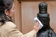 A Japanese rubs the Arai Kannon statue at Toganji Temple, Sugamo, Tokyo, Japan Friday March 11th 2011. Sugamo is affectionately known as the old lady Harajuku, in reference to the Mecca for youth fashions in the South of Tokyo, and is a popular place for Tokyo's increasingly aged population. The Arai Kannon statue is a famous religious icon at Togan-ji temple in the heart of Sugamo, where people go to rub the statue with a white cloth in the hopes of curing sickness and ensuring a long, healthy life.