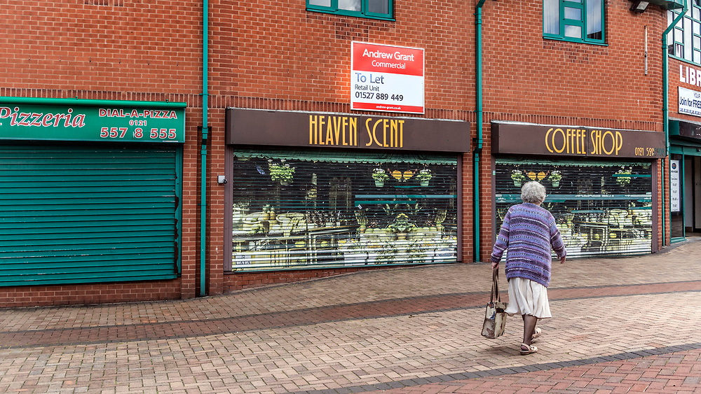 Elderly woman walking past closed down shops in the pedestrian precinct are of Tipton, northwest of Birmingham, West Midlands, UK  With a commerial property let sign in the background.