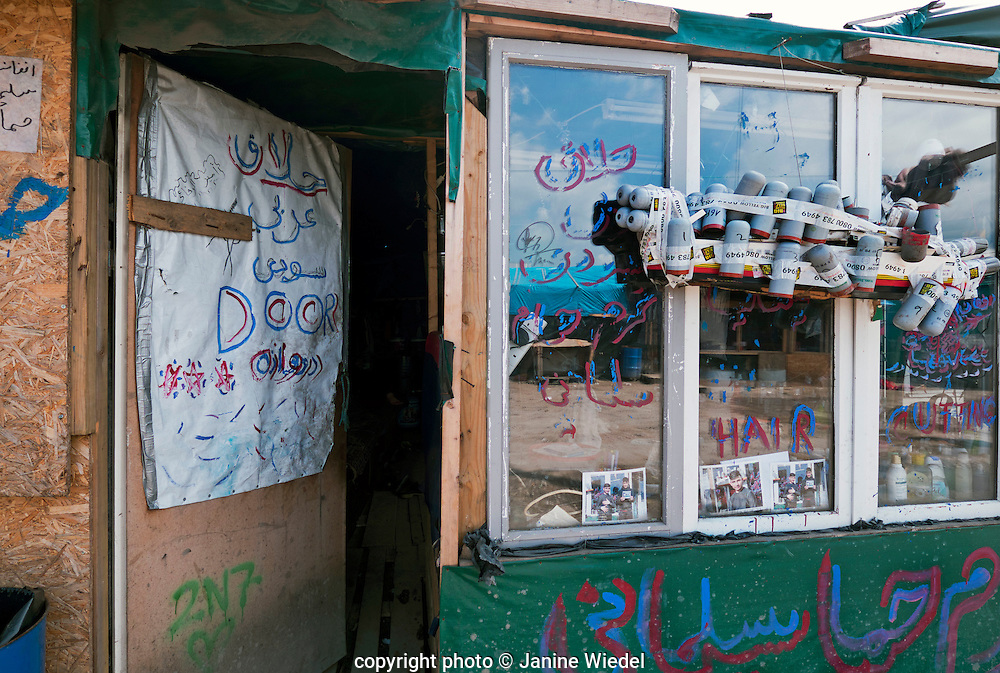 Barbers Shop  in the Calais Jungle Camp where refugees and migrants are living in hope of reaching the UK. Hanging outside are empty tear gas canisters which are continually being let off by the police.