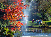 © Licensed to London News Pictures. 27/10/2014. Cliveden, UK. People cross over stepping stone to the chinese water garden.  People walk through the autumnal trees in the morning sunshine at Cliveden House in  Buckinghamshire. Today 27th October 2014. Photo credit : Stephen Simpson/LNP