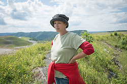 "Marilyn Mullens poses next to a mine on Kayford Mountain in southern West Virginia. She organized the Memorial Day protest against mountaintop-removal mining: ""We just want people to be aware. Know that every time you turn on a light switch . . . someone here is paying for that with dirty water, with air that they can't breathe."" Mountaintop Removal is a method of surface mining that literally removes the tops of mountains to get to the coal seams beneath. It is the most profitable mining technique available because it is performed quickly, cheaply and comes with hefty economic benefits for the mining companies, most of which are located out of state. © Ami Vitale"