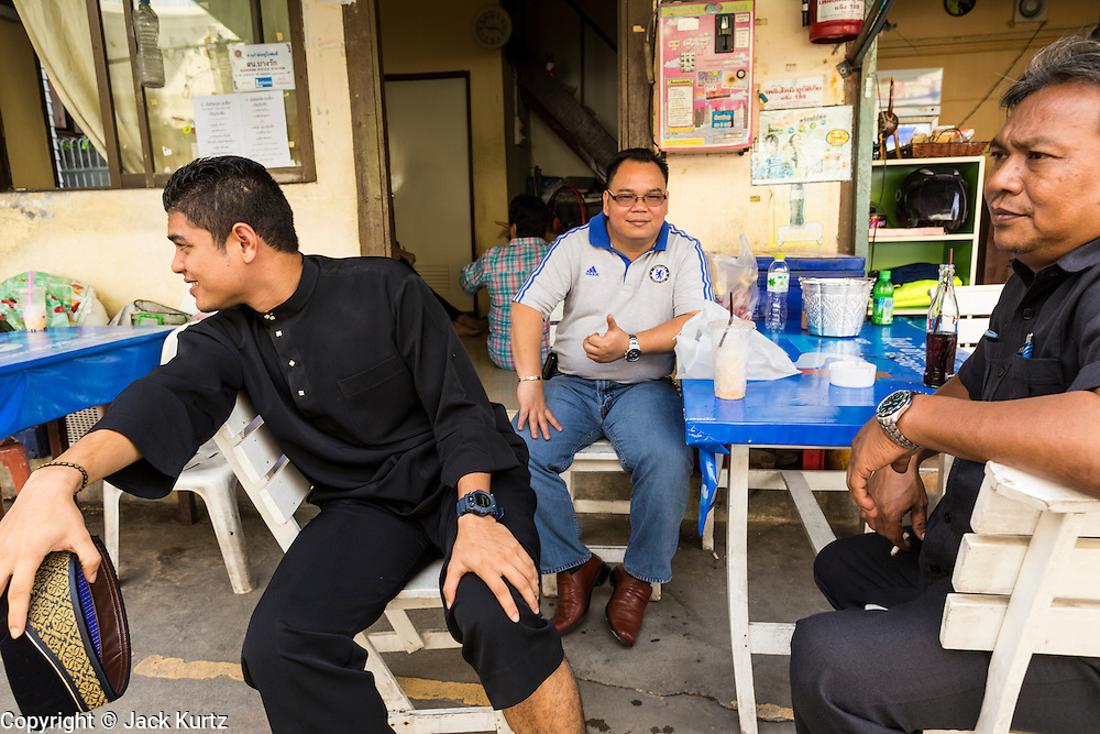 "08 AUGUST 2013 - BANGKOK, THAILAND: Men relax in a small cafe after Eid al-Fitr services near Haroon Mosque in Bangkok. Eid al-Fitr is the ""festival of breaking of the fast,"" it's also called the Lesser Eid. It's an important religious holiday celebrated by Muslims worldwide that marks the end of Ramadan, the Islamic holy month of fasting. The religious Eid is a single day and Muslims are not permitted to fast that day. The holiday celebrates the conclusion of the 29 or 30 days of dawn-to-sunset fasting during the entire month of Ramadan. This is a day when Muslims around the world show a common goal of unity. The date for the start of any lunar Hijri month varies based on the observation of new moon by local religious authorities, so the exact day of celebration varies by locality.      PHOTO BY JACK KURTZ"