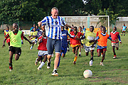 Norman Cook aka DJ Fatboy Slim plays football with the children of the SOS orphanage during a Coaching for Hope training session. Norman is the patron for the charity Coaching for Hope. Coaching for Hope is a project set up to promote awareness of HIV and AIDS through football.