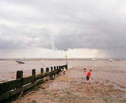 The Red Arrows, Britain's RAF aerobatic team, perform their public display over a landscape of the Thames estuary mud.