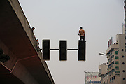 CHANGSHA, CHINA - MAY 24: (CHINA OUT) <br /> <br /> A man naked back stands on a signal lamp as he is about to jump for suicide on May 24, 2016 in Changsha, Hunan Province of China. The police officers, fire workers and traffic police have set up mattresses but the man jump on ground. An ambulance has carried the man to nearby hospital and his suicide reasons was unknown by the press time<br /> ©Exclusivepix Media