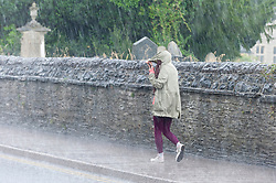 © Licensed to London News Pictures.28/07/2021. Builth Wells, Powys, Wales, UK. A young woman walks along a rainy street with her mobile phone during a thunderstorm at Builth Wells in Powys, UK. Photo credit: Graham M. Lawrence/LNP