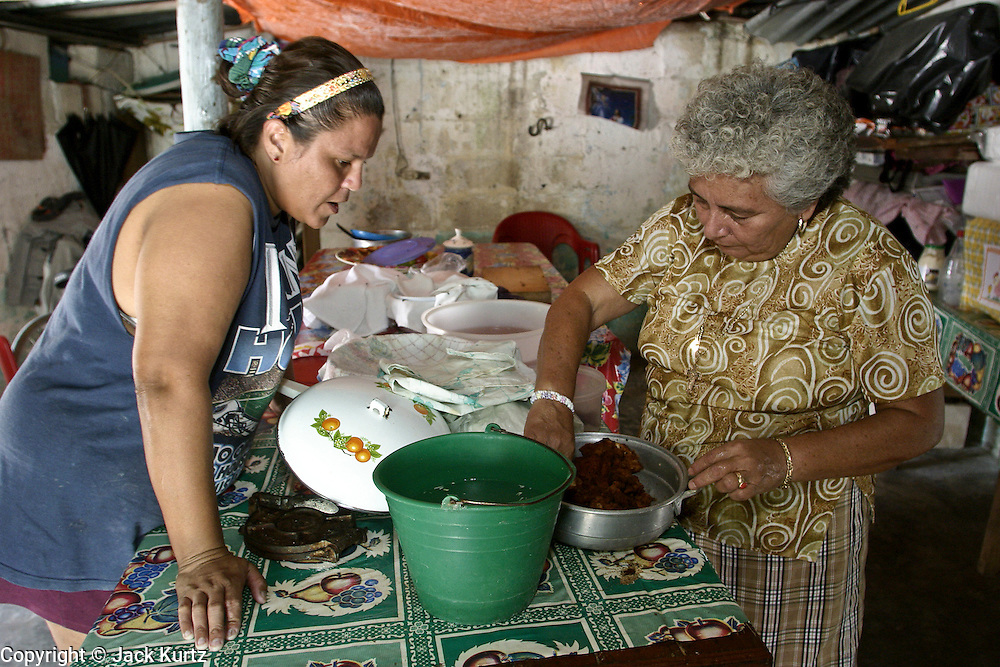 09 SEPTEMBER 2003 - CANCUN, QUINTANA ROO, MEXICO: Guadalupe Pacheco Medino, RIGHT, prepares a take out dinner of chicken and tortillas for a customer in the Medino home in Cancun, Quintana Roo, Mexico, Sept 9, 2003. Medino supplement her family's income by preparing takeout meals for her neighbors. Her husband is a retired fisherman who also worked in the tourist industry before he was forced to retire for health reasons. Her sons still fish from open boats in the waters off Cancun. The family has lived in the region for years, since before Cancun was Cancun and was a small fishing community called Puerto Juarez. PHOTO BY JACK KURTZ  economy  labour  food  women  poverty  culture