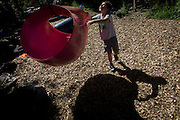 Boy plays with rope swing in risk averse playground called The Land on Plas Madoc Estate, Ruabon, Wrexham, Wales.