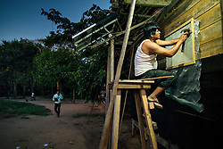 NO WEB/NO APPS - Exclusive. (Text available) A man installs mosquito nets at the windows of his home, in 'Palma Real' native community, near Puerto Maldonado, Peru on July 17, 2017. The Amazon rainforest is famous as 'The Lung of the Earth', but also for the presence of numerous native communities, who have always lived isolated and in close contact with nature for generations, used to seek for food and medicines and to build items directly from the environment in which they live. The unstoppable rise of globalization has drastically changed their needs, expectations and consequently their way of life. Located in the Tambopata National Reserve, on the border between Peru and Bolivia, the native Comunidad Palma Real is one of the clearest examples of this change. Living on the banks of the Madre de Dios River since approximately 1976, Palma Real comprises about 300 people part of the nomadic community Ese-Eja, established in the Amazon rainforest of Peru before the Spanish colonization. Photo by Giacomo d'Orlando/ABACAPRESS.COM