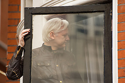Julian Assange returns inside after speaking from the balcony of the Ecuadorian embassy in London after a seven-year investigation in Sweden against the WikiLeaks founder was suddenly dropped.