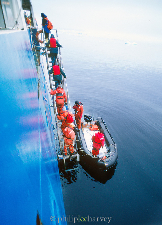 Tourists rejoin large vessal after whale watching trip, Antarctica
