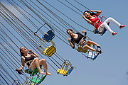 Three visitors get a thrill on a carnival ride at the Strawberry Festival in Garden Grove, CA during the Memorial Day weekend.