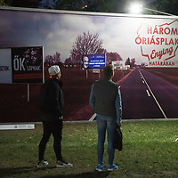 """Visitors watch a politics themed billboard reacting in Hungarian to the movie title """"Three Billboards Outside Ebbing"""" at the Arc Billboard social issues exhibition in Budapest, Hungary on Sept. 24, 2018. ATTILA VOLGYI"""
