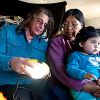 032713     Brian Leddy<br /> Marsha Monestersky shows a small rechargeable solar light to Etta Wilson at her home near Bodaway Gap Wednesday, March 27.