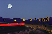 The road to Los Alamos, New Mexico, with a full moon above a dangerous curve. (1988)