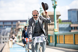 © Licensed to London News Pictures. 04/05/2019. London, UK. A man raises his hat as he cycles across Southwark Bridge on the Tweed Run bike ride in Central London. The annual event sees hundreds of people cycle around the capital past various landmarks wearing vintage tweed outfits. Photo credit: Rob Pinney/LNP