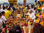 15 NOVEMBER 2018 - BANGKOK, THAILAND: People pick up fruit and flowers that have been blessed during the red cloth ceremony at Wat Saket, also called the Golden Mount. Wat Saket is on a man-made hill in the historic section of Bangkok. The temple has golden spire that is 260 feet high, which was the highest point in Bangkok for more than 100 years. The temple construction began in the 1800s during the reign of King Rama III and was completed in the reign of King Rama IV. A  red cloth (reminiscent of a monk's robe) is placed around the chedi at the top of  Golden Mount during the weeks leading up to the Thai holy day of Loy Krathong, which is November 22 this year.      PHOTO BY JACK KURTZ