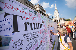 © Licensed to London News Pictures. 13/07/2018. London, UK. People write messages for Donald Trump alongside an open letter from Avaaz as thousands of protesters march through central London against the President of the United States of America Donald Trump's visit to the United Kingdom. Photo credit: Rob Pinney/LNP