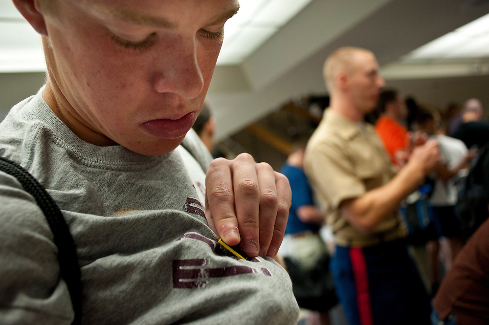 """A freshman pins on his nametag during processing on his first day at the U.S. Naval Academy in Annapolis, MD. Approximately 1,230 young men and women arrived at the U.S. Naval Academy's Alumni Hall, Thursday, July 1, for Induction Day to begin their new lives as """"plebes"""" or midshipmen fourth class (freshmen). """"I-Day"""" culminates when the members of the Class of 2014 take the oath of office at a ceremony at 6 p.m. in Tecumseh Court, the historic courtyard of the Bancroft Hall dormitory. Over 17,400 young men and women applied to be members of the Naval Academy Class of 2014 - a record for USNA."""
