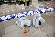 Extinction Rebellion 'crime scene investigators' in white suits and masks put up climate crime scene tape to gather evidence in areas of ecocide in a performance in Parliament Square in an area already cordoned off on 7th September 2020 in London, United Kingdom. The 20 investigators were protesting at the UK government's ecocide along the HS2 route. Extinction Rebellion is a climate change group started in 2018 and has gained a huge following of people committed to peaceful protests. These protests are highlighting that the government is not doing enough to avoid catastrophic climate change and to demand the government take radical action to save the planet.