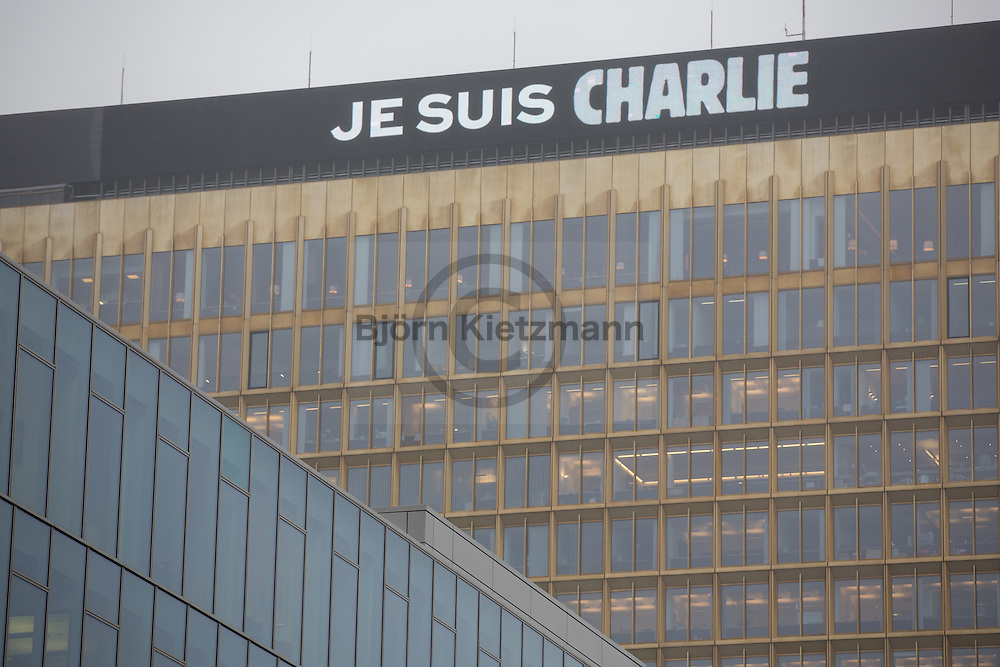 """Berlin, Germany -  08.01.2015 <br /> <br /> Day after the Islamistic terrorist attack on the French satirical magazine Charlie Hebdo. The billboard of the Axel Springer tower in Berlin shows the statement """"Je suis Charlie""""<br /> <br /> Am Tag nach dem islamistischen Terroranschlag auf das Satire Magazin Charlie Hebdo. Am Axel Springer Hochhaus zeigt die Werbetafel die Aussage """"Je suis Charlie"""".<br /> <br /> Photo: Bjoern Kietzmann"""