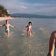 A young asian family enjoy the pristine waters of White Beach, Boracay Island, the Philippines on October 4, 2008, Photo Tim Clayton..Asian tourists at White Beach, Boracay Island, the Philippines...The 4 km stretch of White beach on Boracay Island, the Philippines has been honoured as the best leisure destination in Asia beating popular destinations such as Bali in Indonesia and Sanya in China in a recent survey conducted by an International Travel Magazine with 2.2 million viewers taking part in the online poll...Last year, close to 600,000 visitors visited Boracay with South Korea providing 128,909 visitors followed by Japan, 35,294, USA, 13,362 and China 12,720...A popular destination for South Korean divers and honeymooners, Boracay is now attracting crowds of tourists from mainland China who are arriving in ever increasing numbers. In Asia, China has already overtaken Japan to become the largest source of outland travelers...Boracay's main attraction is 4 km of pristine powder fine white sand and the crystal clear azure water making it a popular destination for Scuba diving with nearly 20 dive centers along White beach. The stretch of shady palm trees separate the beach from the line of hotels, restaurants, bars and cafes. It's pulsating nightlife with the friendly locals make it increasingly popular with the asian tourists...The Boracay sailing boats provide endless tourist entertainment, particularly during the amazing sunsets when the silhouetted sails provide picture postcard scenes along the shoreline...Boracay Island is situated an hours flight from Manila and it's close proximity to South Korea, China, Taiwan and Japan means it is a growing destination for Asian tourists... By 2010, the island of Boracay expects to have 1,000,000 visitors.