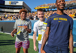 Sep 11, 2021; Morgantown, West Virginia, USA; Former West Virginia Mountaineers basketball player and current New York Knick Miles McBride (left) reacts to a touchdown with former teammates during the first quarter against the Long Island Sharks at Mountaineer Field at Milan Puskar Stadium. Mandatory Credit: Ben Queen-USA TODAY Sports