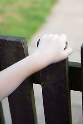 Child's hand on a gate,