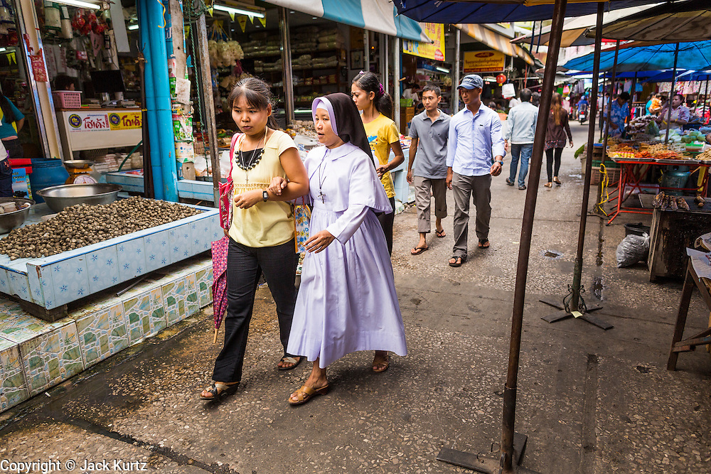23 MAY 2013 - MAE SOT, TAK, THAILAND: A Catholic nun and a friend walk through the Burmese market in Mae Sot, Thailand. Fifty years of political turmoil in Burma (Myanmar) has led millions of Burmese to leave their country. Many have settled in neighboring Thailand. Mae Sot, on the Mae Nam Moei (Moei River) is the center of the Burmese emigre community in central western Thailand. There are hundreds of thousands of Burmese refugees and migrants in the area. Many live a shadowy existence without papers and without recourse if they cross Thai authorities. The Burmese have their own schools and hospitals (with funding provided by NGOs). Burmese restaurants and tea houses are common in the area.    PHOTO BY JACK KURTZ
