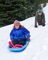 Father and daughter sledding in the mountains