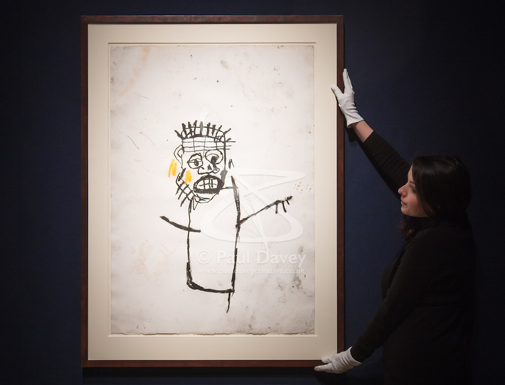 Christie's, London, March 3rd 2017. PICTURED: A gallery worker straightens Jean-Michel Basquait's Untitled piece from 1982, oil stick on paper, with is expected to fetch between £1-1.5million. <br /> Fine art auctioneers Christies hold a press preview for their Post-War and Contemporary Art auctions to be held on March 7th and 8th.