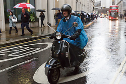 © Licensed to London News Pictures. 08/09/2017. LONDON, UK.  A man on a scooter wearing a rain poncho near Liverpool Street station in London during rain and wet weather.  Photo credit: Vickie Flores/LNP