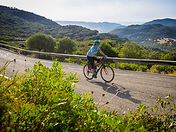 Scenic view of woman riding bike against mountain forest