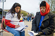 """02 JANUARY 2008 -- PHOENIX, AZ: ROSIE VILLEGAS-SMITH (left) and ISABEL GALINDO, immigrant rights activists, pray for peace and immigration reform in front of the Macehualli Work Center while anti-immigrant protestors picket the center behind them. Anti-immigration protestors who had been staging demonstrations in central Phoenix have moved their pickets to the Macehualli Work Center in north Phoenix. The work center is a pick up and staging area for day laborers, many of whom are illegal immigrants. The protestors hope that they can shut down the center by photographing and videotaping people who come and go from the center, both those looking for work and those looking for workers. The picketers, from a variety of anti-immigration groups, have promised to turn their photos and video tapes over to the Maricopa County Attorney for use in prosecuting immigration and employer sanctions crimes. The picketers vow to stay at the center until it closes. A new """"employer sanctions"""" law became active in Arizona on January 1, 2008. Upon the first conviction, the law suspends the business license of any business that knowlingly hires an illegal worker and permanently revokes the business license of a business convicted a second time of hiring an illegal worker. The law is widely seen as being the toughest anti-immigrant law in the US and is being contested in federal court by a coalition of Arizona businesses.   Photo by Jack Kurtz"""