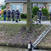 Lijnden, 07-11-2012. Ambulances, Traumahelikopter, Brandweer en politie rukten vanmiddag massaal uit na een melding dat een man mogelijk te water was geraakt. Eerder die dag werd een man gezien met een fiets die steeds viel. Even later werd slechts de fiets lang het water aan de Hoofdweg te Lijnden aangetroffen. Van de man was geen spoor te bekennen. Duikers van de Brandweer zochten rond de plaats waar de fiets werd aangetroffen de Hoofdvaart af. Rond 14.30 uur werd het zoeken gestaakt. Op de foto staat de bedoelde fiets tegen een boom. 3de persoon van links John Jones Foto JOVIP/JOHN VAN IPEREN